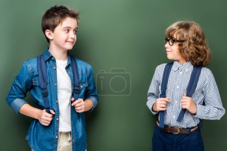 schoolboys with backpacks looking at each other near blackboard