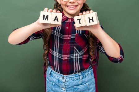 Photo for Cropped image of schoolchild holding wooden cubes with word math near blackboard - Royalty Free Image