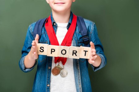 cropped image of schoolboy with medals holding wooden cubes with word sport near blackboard