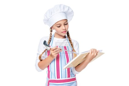 schoolchild in costume of chef reading recipe book isolated on white