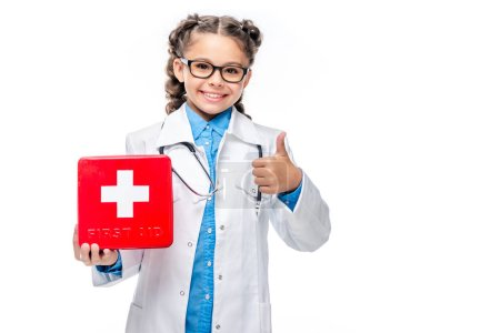 schoolchild in costume of doctor holding first aid kit and showing thumb up isolated on white