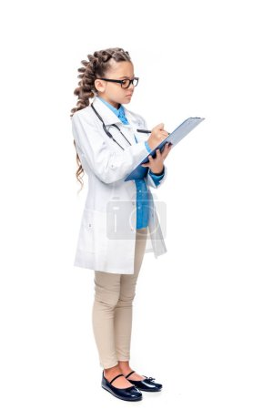 side view of schoolchild in costume of doctor writing something to clipboard isolated on white