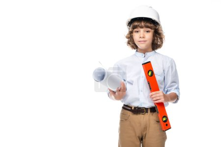 schoolboy in costume of architect and helmet holding blueprints and spirit level isolated on white