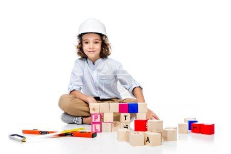 Photo pour Lycéen en costume de l'architecte et casque assis près des cubes en bois, isolés sur blanc - image libre de droit