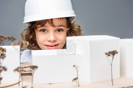 schoolboy in costume of architect near model of buildings isolated on white