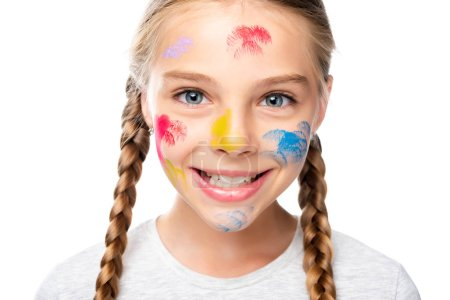 portrait of smiling schoolchild with paints on face looking at camera isolated on white