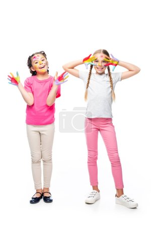 happy schoolchildren having fun with painted hands and faces isolated on white