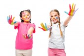 schoolchildren showing painted colorful hands and looking at camera isolated on white