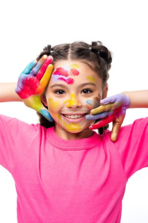 adorable schoolchild touching face with painted hands isolated on white