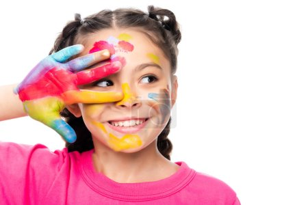 portrait of smiling schoolchild with painted face and hand looking away isolated on white