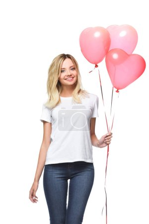 happy attractive girl in white shirt holding bundle of heart shaped balloons isolated on white