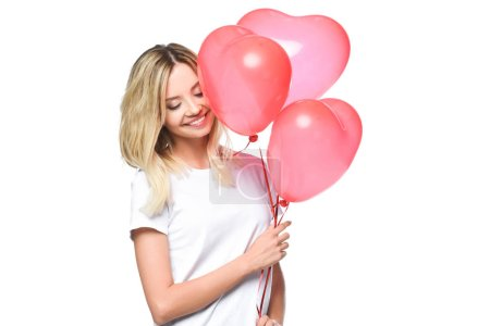 attractive girl in white shirt holding bundle of heart shaped balloons isolated on white