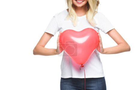 cropped image of smiling girl in white shirt holding heart shaped balloon isolated on white