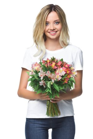 smiling attractive girl holding bouquet of flowers and looking at camera isolated on white