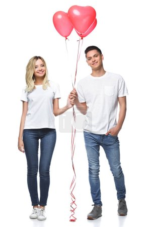 couple standing with bundle of heart shaped balloons and looking at camera isolated on white