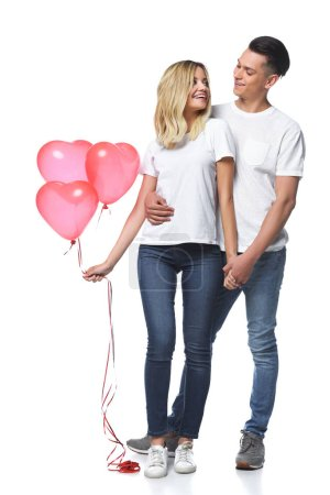 couple standing with bundle of heart shaped balloons and looking at each other isolated on white