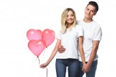 couple standing with bundle of heart shaped balloons isolated on white