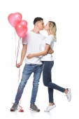 couple kissing, boyfriend holding bundle of heart shaped balloons isolated on white