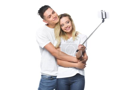 Photo for Happy couple taking photo with smartphone and selfie stick isolated on white - Royalty Free Image