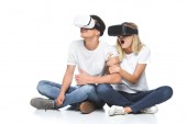 shocked couple using virtual reality headsets isolated on white
