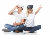 couple using virtual reality headsets isolated on white, girlfriend pointing on something