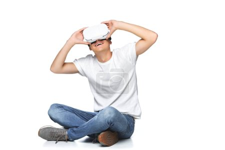 smiling handsome man in white shirt using virtual reality headset isolated on white