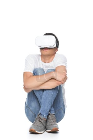 handsome man in white shirt sitting scared with virtual reality headset isolated on white