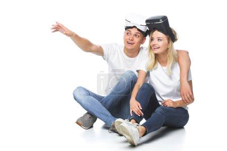 Photo pour Couple assis avec les casques de réalité virtuelle et à la recherche de loin isolé sur blanc - image libre de droit