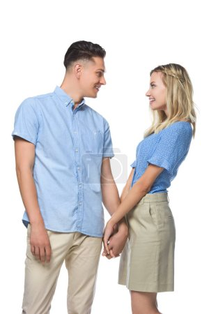 smiling couple in blue shirts holding hands and looking at each other isolated on white