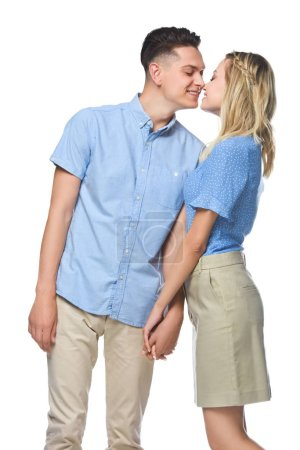 smiling couple in blue shirts kissing isolated on white