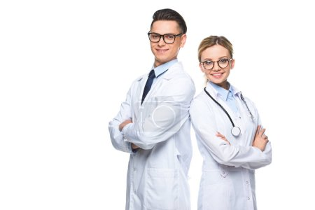 smiling doctors standing with crossed arms and looking at camera isolated on white