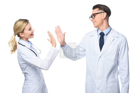 general practitioners in white coats giving highfive, isolated on white