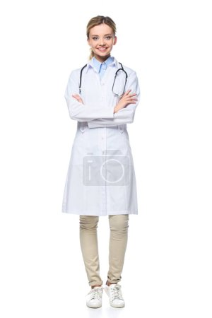 young female doctor in white coat posing with crossed arms, isolated on white