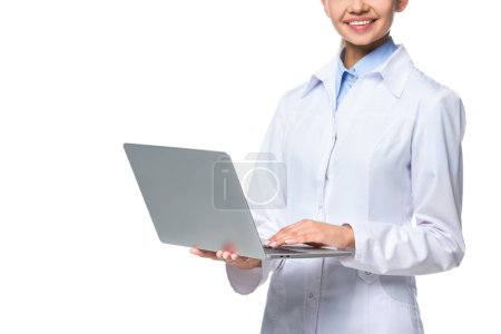 Photo for Cropped view of female doctor in white coat using laptop, isolated on white - Royalty Free Image
