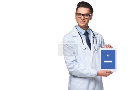 handsome young doctor holding tablet with facebook app on screen isolated on white