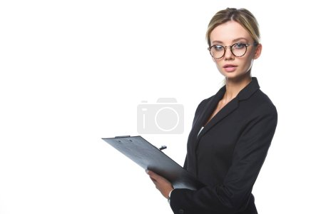 confident young businesswoman holding clipboard and looking at camera isolated on white