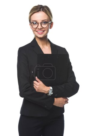 smiling young businesswoman holding clipboard and looking at camera isolated on white