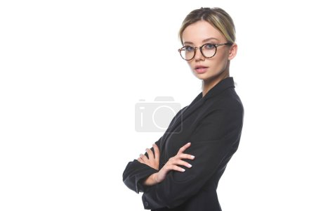 confident young businesswoman in suit and eyeglasses looking at camera with crossed arms isolated on white
