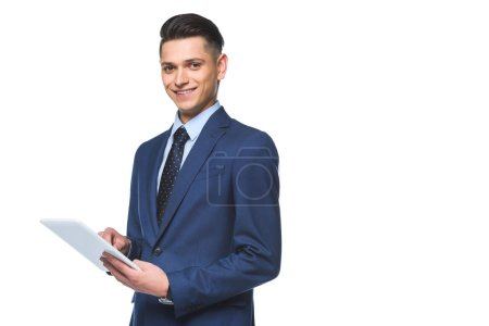 happy young businessman in stylish blue jacket using tablet and looking at camera isolated on white