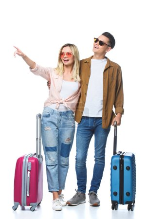 young travelling couple with suitcases pointing somewhere isolated on white