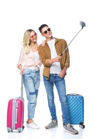 jeune couple avec valises prenant selfie avec smartphone de monopode isolé sur blanc