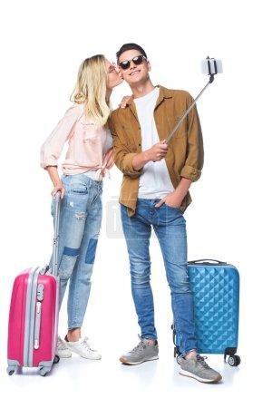 Photo pour Jeune couple avec valises prendre selfie de monopode tandis que la femme embrasser son petit ami isolé sur blanc - image libre de droit