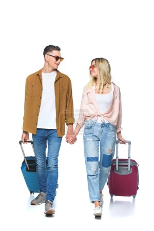 young travelling couple holding hands and walking with suitcases isolated on white