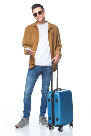 happy young man with luggage and smartphone isolated on white