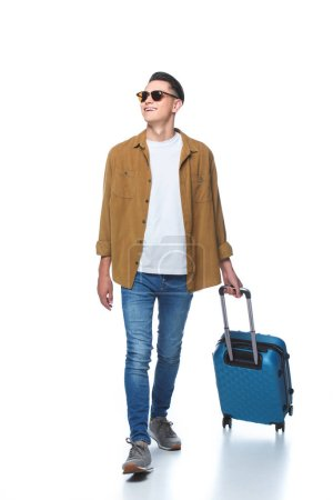 happy young man walking with luggage isolated on white