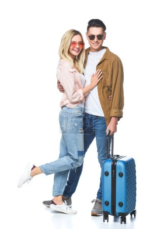 beautiful young woman embracing her boyfriend while he standing with suitcase isolated on white
