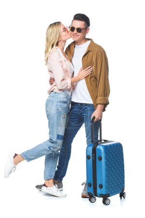 beautiful young woman kissing her boyfriend while he standing with suitcase isolated on white