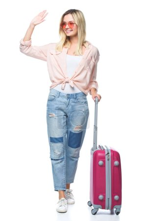 young travelling woman with luggage waving wih hand isolated on white