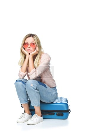 young bored woman sitting on luggage isolated on white