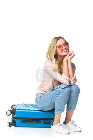 Photo pour Jeune femme heureuse assise sur des bagages isolés sur blanc - image libre de droit